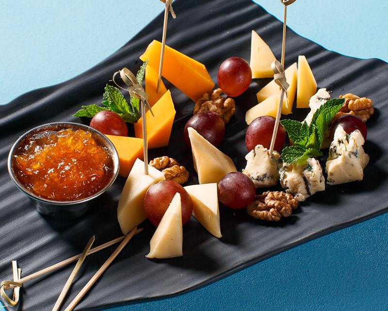 Сырная тарелка с виноградом, орехом и абрикосовым джемом