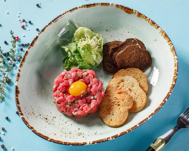 Тартар из говядины с хлебными чипсами и листьями салата